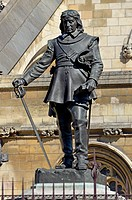 London, England, UK. Statue (William Hamo Thornycroft; 1899) of Oliver Cromwell (1599-1658) in front of Parliament.