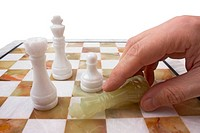 hand poses a chess piece on the board