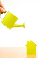 Conceptual picture of a watering can and little house