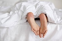 Shot of a pair of woman's feet poking out from under the sheets of a bed