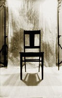 Black and white infrared shot of black chair in front of backdrop in studio.