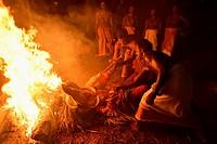 India, Kerala, Kannur region, Mundiyat Bhagavathi temple, Pottan Theyyam lying and burning (!) on a pyre.