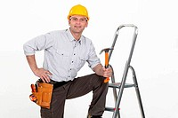 Handyman posing with his tools and a stepladder