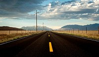 a roadway in a countryside with mountains