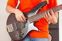 Hands of guitarist playing the bass guitar