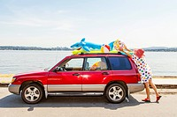 Woman takes beach toys and floaties off the roof of a car
