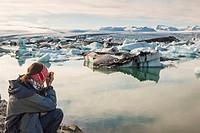 Photographer on coast of Jokulsarlon lagoon - Iceland.
