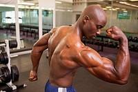 Rear view of shirtless muscular man flexing muscles