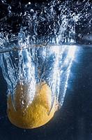 Lemon plunging into liquid