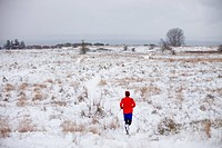 Jogger running through snow covered park