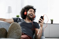 Laughing young man lying on couch at home listening music with headphones and smartphone
