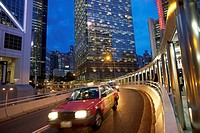 dusk traffic on curved, elevated roadway in the Admiralty district, with sections of Bank of China Tower and Chung Kong Centre buildings, Hong Kong.