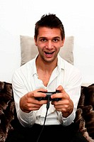 Smiling Gamer sitting on couch with controller and playing