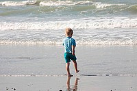 young child walking on the sand to the waves