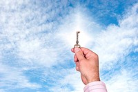 Man holding up key against bright sky