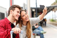 Couple of travelers photographing a selfie with a smartphone