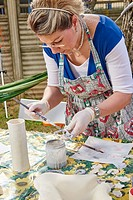 An amateur artist apply raku glaze on ceramic object.