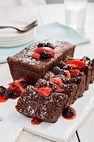 Sliced chocolate cake with strawberries and blackberries