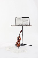 a violin next to note papers