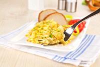 Scrambled eggs on fork.