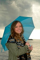 Smiling young woman with blue umbrella a rainy day at the sea in Ystad, Sweden.