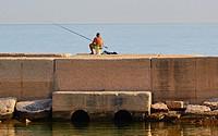 Man fishing from pier, Molfetta, Puglia, Italy, Europe.