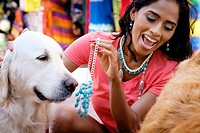Hispanic woman trying on jewelry while playing with dogs at a street market in Puerto Vallarta, Mexico.