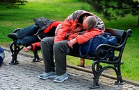 Two homeless persons sleep on a bench in Swinoujscie; Western Pomerania, Poland.