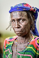 Portrait of a Mbororo woman with scars on her face dressed in a very colourful outfit.