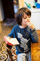 Child sitting at the kitchen table with a book in hand