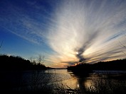 A large cloud forms over a lake at sunset and commands the sky, Pennsylvania, USA.