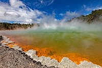 Champagne pool, burst of sunshine lights up foreshore during day of blowing mist and heavy rain, Wai-o-Tapu thermal region, Rotorua.