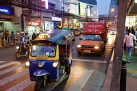 tuk tuk taxi, motorcyle and utility transport at lights in downtown Bangkok.