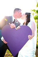 bride & groom on wedding day kissing while holding a big heart