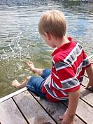 A boy kicks his feet in the water at Liberty Lake, Washington, USA.