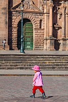 Young Peruvian child walking across the road in the Plaza de Armas, Cusco, Peru.