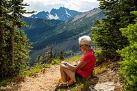 A woman, 69, looks at a map as she sits on a path in the Cascade Mountains of Washington state, USA