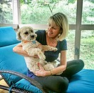 Blonde woman holding a cute white dog on her lap.