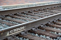 """Flagstaff, Arizona - A stenciled """"""""No Trespassing"""""""" sign on the busy BNSF railroad tracks in downtown Flagstaff."""