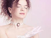 Closeup face portrait of young beautiful woman wearing a lace choker with pink rose and white lacy gloves on pink background.