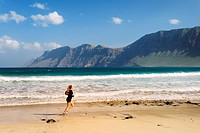 Young woman running jogging on beach Playa at La Caleta de Famara with cliffs of Risco de Famara. Lanzarote, Canary Islands.