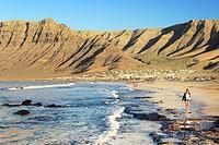 Young woman walking on beach Playa at La Caleta de Famara with cliffs of Risco de Famara. Lanzarote, Canary Islands.