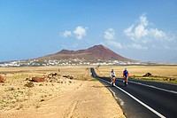 Cycling on the LZ-401 road from volcanic cone rising above village of Soo. Teguise, Lanzarote, Canary Islands, Spain.