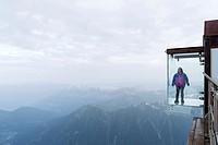 Woman in a crystal box on the void, Pas dans le Vide - step into the void - at 3842 m, Aiguille du Midi, Chamonix-Mont-Blanc, Haute-Savoie, France, Eu...