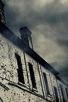 Spooky dilapidated brick building with long windows under menacing gathering storm clouds. Atmospheric eerie housing details.