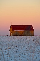 rustic barn in a snow field.