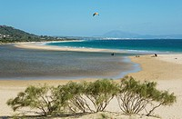 Sandy beaches with kitesurfer at the Bay of Valdevaqueros. In the background the town of Tarifa and the Rif Mountains in Morocco, separated by the Str...