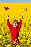boy with long blond hair playing with pinwheels in canola field.