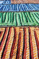 Coloured cotton sari fabric drying outside factory in sun Jetpur Gujarat India.