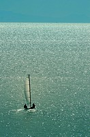 Small sail boat heading to the sea away from the shore.